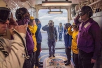 Japan Maritime Self-Defense Force (JMSDF) Rear Adm. Shirane Tsutomu, commander, JMSDF Mine Warfare Force, salutes sideboys during an underway visit to amphibious assault ship USS America (LHA 6).