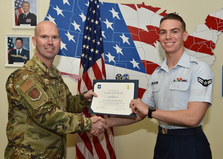 U.S. Air Force Lt. Col. Kevin Boss, 17th Training Group deputy commander, presents the 316th Training Squadron Student of the Month award to Airman 1st Class Jason Skendrovich, 316th TRS student, at Brandenburg Hall on Goodfellow Air Force Base, Texas, Jan. 10, 2019. The 316th TRS's mission is to conduct U.S. Air Force, U.S. Army, U.S. Marine Corps, U.S. Navy and U.S. Coast Guard cryptologic, human intelligence and military training. (U.S. Air Force photo by Staff Sgt. Chad Warren)