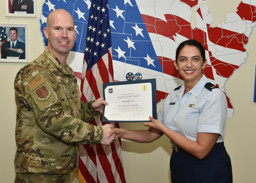 U.S. Air Force Lt. Col. Kevin Boss, 17th Training Group deputy commander, presents the 315th Training Squadron Officer Student of the Month award to 2nd Lt. Melissa Levison, 315th TRS student, at Brandenburg Hall on Goodfellow Air Force Base, Texas, Jan. 10, 2020. The 315th TRS's vision is to develop combat-ready intelligence, surveillance and reconnaissance professionals and promote an innovative squadron culture. (U.S. Air Force photo by Staff Sgt. Chad Warren)