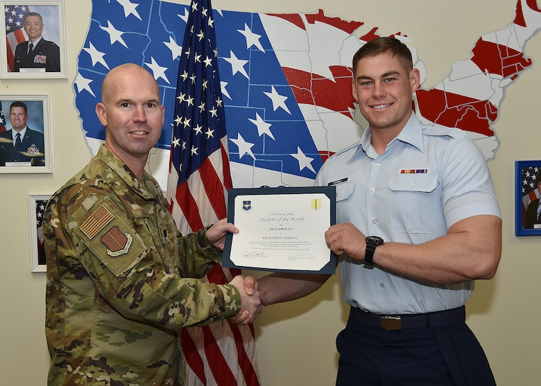 U.S. Air Force Lt. Col. Kevin Boss, 17th Training Group deputy commander, presents the 312th Training Squadron Student of the Month award to Airman Basic Jeffrey Farrell, 312th TRS student, at Brandenburg Hall on Goodfellow Air Force Base, Texas, Jan. 10, 2020. The 312th TRS's mission is to provide Department of Defense and international customers with mission-ready fire protection and special instruments graduates and provide mission support for the Air Force Technical Applications Center. (U.S. Air Force photo by Staff Sgt. Chad Warren)