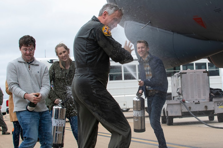 Friends and family spray Col. Burgess with water as he laughs.