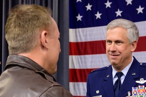 Photo of two Airmen speaking.