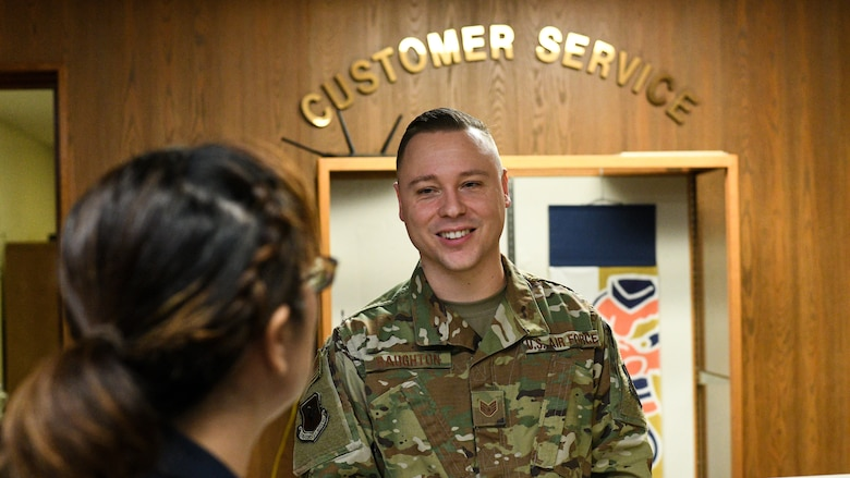U.S. Air Force Staff Sgt. Benjamin Raughton, 18th Wing Public Affairs photographer, greets a Japanese customer at Kadena Air Base, Japan, Jan. 8, 2020. Raughton's ability to communicate in Japanese with the local population stems from the video games that now rest in his office. (U.S. Air Force photo by Tech. Sgt. Hugo Delgado)