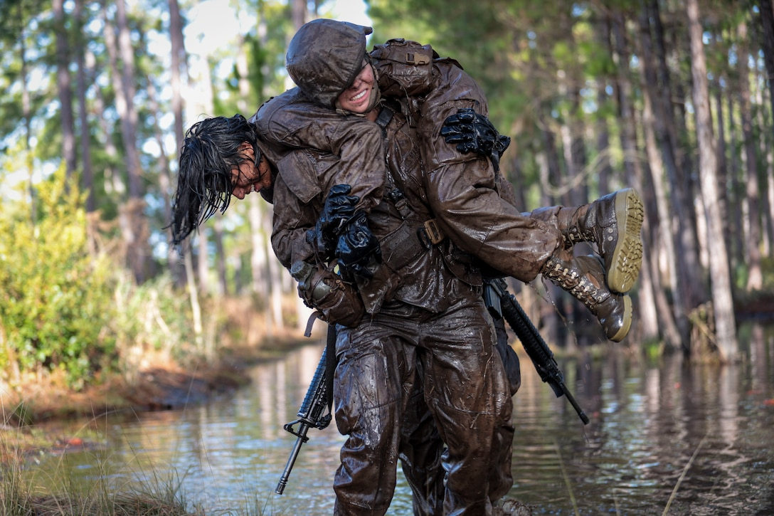 A Marine carries another Marine over her shoulder through a muddy swamp.