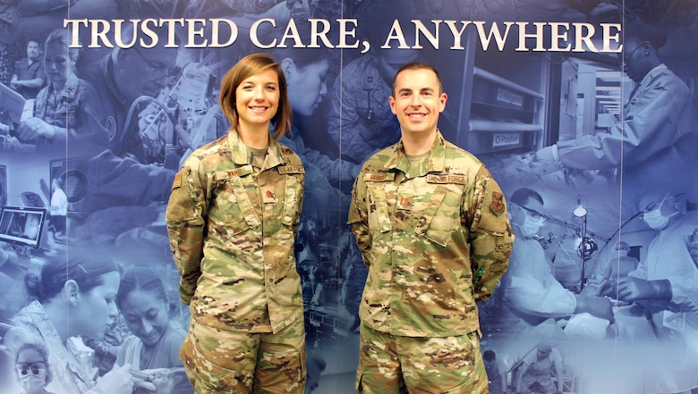 Image of two Airmen standing in front of a mural.