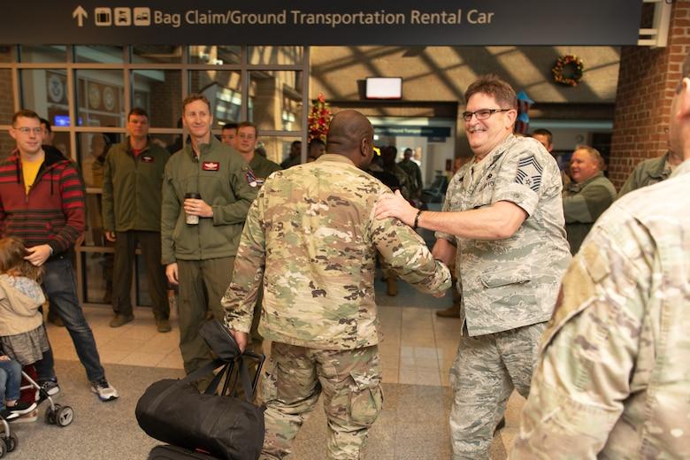 Airmen at an airport return from a deployment