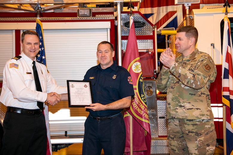 Robert Smith, center, 423rd Civil Engineer Squadron firefighter, receives a Chief Fire Officer's commendation at RAF Alconbury, Dec. 20, 2019. Smith was recognized for exemplary lifesaving abilities under extreme pressure and clarity of mind for actions performed on August 21st. Smith administered CPR to his wife Karen for 17 minutes until paramedics arrived at his home. (U.S. Air Force photo by Senior Airman Eugene Oliver)
