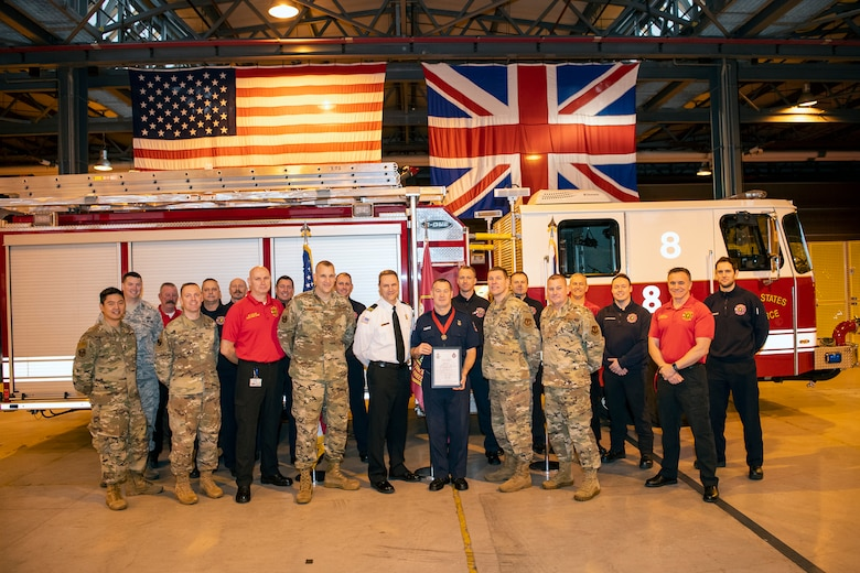 Robert Smith, center, 423rd Civil Engineer Squadron firefighter, poses for a photo along with firefighters and leadership from the 423d CES and 501st Combat Support Wing after receiving a Chief Fire Officer's commendation medal at RAF Alconbury, Dec. 20, 2019. Smith was recognized for exemplary lifesaving abilities under extreme pressure and clarity of mind for actions performed on August 21st. Smith administered CPR to his wife Karen for 17 minutes until paramedics arrived at his home. (U.S. Air Force photo by Senior Airman Eugene Oliver)