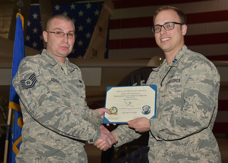 Capt. Shawn Lundskow, 552nd Maintenance Squadron/White Aircraft Maintenance Unit Officer in Charge, presents a dedicated crew chief certificate to Tech. Sgt. Clinton Ashley, 552nd MXS, during an E-3 Sentry aircraft dedication ceremony held Jan. 6, 2020 in Dock 2 of Bldg. 230. This marks the first time that the 966th Airborne Air Control Squadron had an E-3 Sentry aircraft dedicated for use by the squadron and will help forge a bond between aircrews and maintainers.