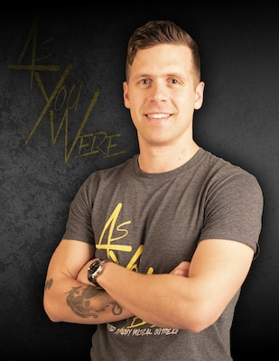 Brown-haired man with crossed arms and tattoo on right arm with gray t-shirt with yellow lettering against a gray background with yellow letters that say As You Were.