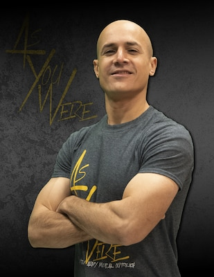 Bald male with arms crossed in grey t-shirt with yellow words with a black background and words that say As you Were.