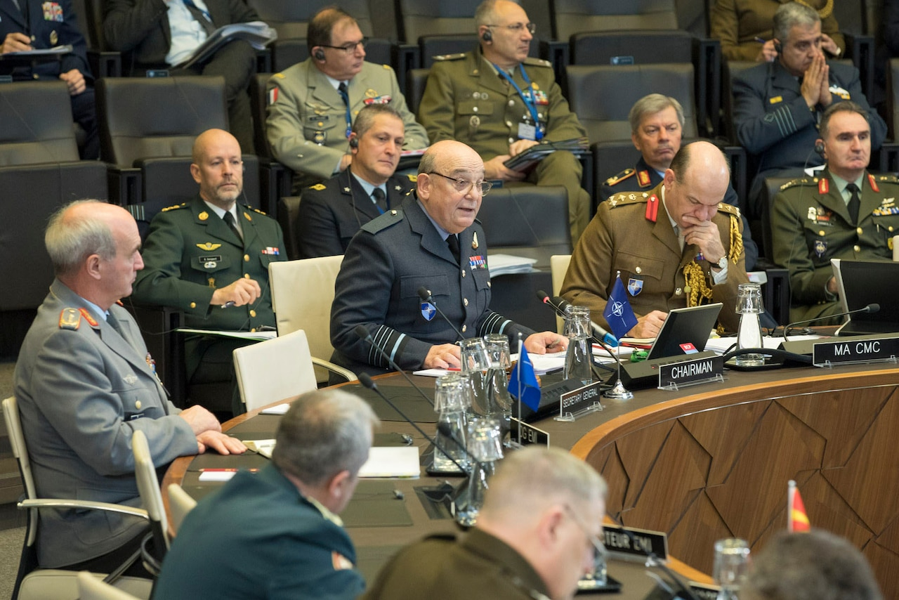 Military officers from various nations sit behind microphones at a round table.