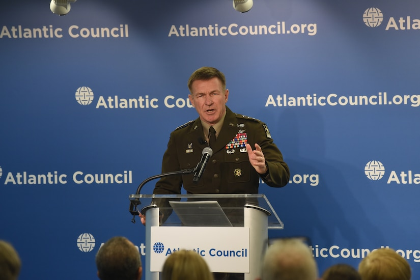 A military officer speaks from behind a podium.