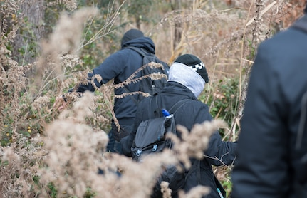 Volunteers simulating hostile individuals, search a field for U.S. Air Force personnel during a training at Joint Base Langley-Eustis, Virginia, Dec. 12, 2019. The training taught participants camouflaging, evasion and other skills necessary in the event of an isolating situation. U.S. Air Force photo by Airman 1st Class Sarah Dowe)