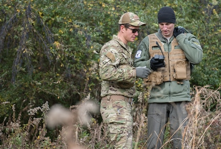 U.S. Air Force Tech. Sgt. Stephen Drakes, 192 Operations Support Squadron, Virginia Air National Guard SERE Survival, Evasion, Resistance and Escape non-commissioned officer in charge, watches as Capt. Nathan Miller, 94th Fighter Squadron instructor pilot, demonstrates how to work a survival radio during a training at Joint Base Langley-Eustis, Virginia, Dec. 12, 2019. Participants used the equipment they would have in an isolation situation. (U.S. Air Force photo by Airman 1st Class Sarah Dowe)