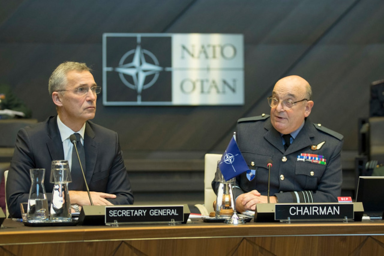 A civilian wearing a suit and a military officer in uniform sit behind microphones with a NATO emblem behind them.