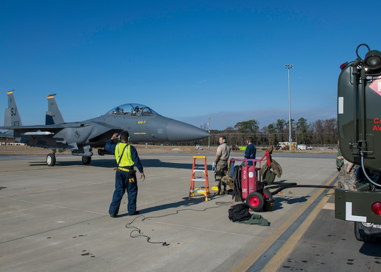 Airmen from the 4th Logistics Readiness Squadron marshal an F-15E Strike Eagle to an R-11 fuel truck for hot-pit refueling.
