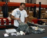 Korey Leese, material handler supervisor for Defense Logistics Agency Distribution, assembles a combat medical kit, one of several types of kits the agency provides. Medical kit assemblies range in size from small first aid kits to large mobile field hospitals, and may include both medical and nonmedical items.