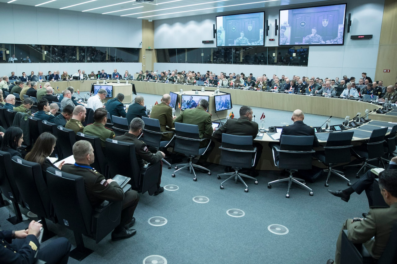 Wide-angle shot of a large conference facility, dominated by a round table with military officers seated around it.
