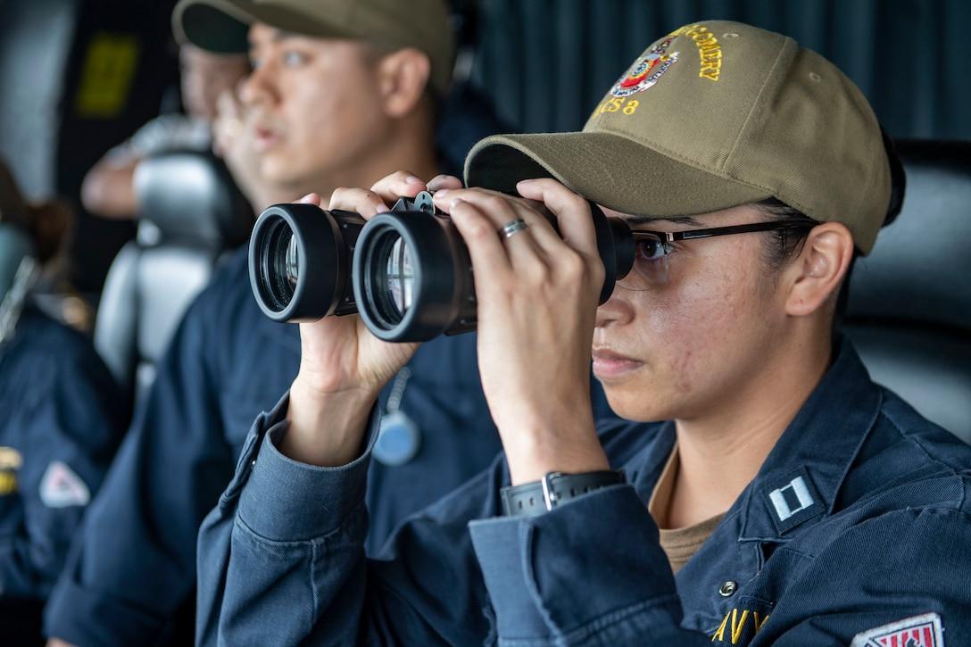 A sailor looks through binoculars.
