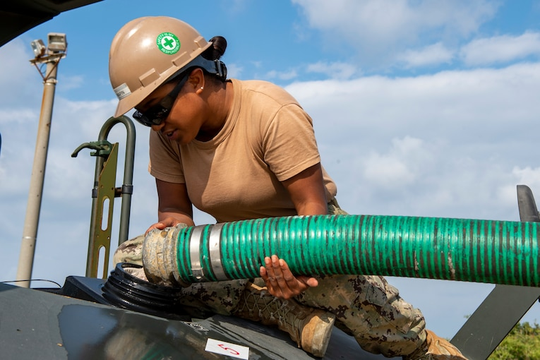A service member holds a large hose to pour water into a vehicle.