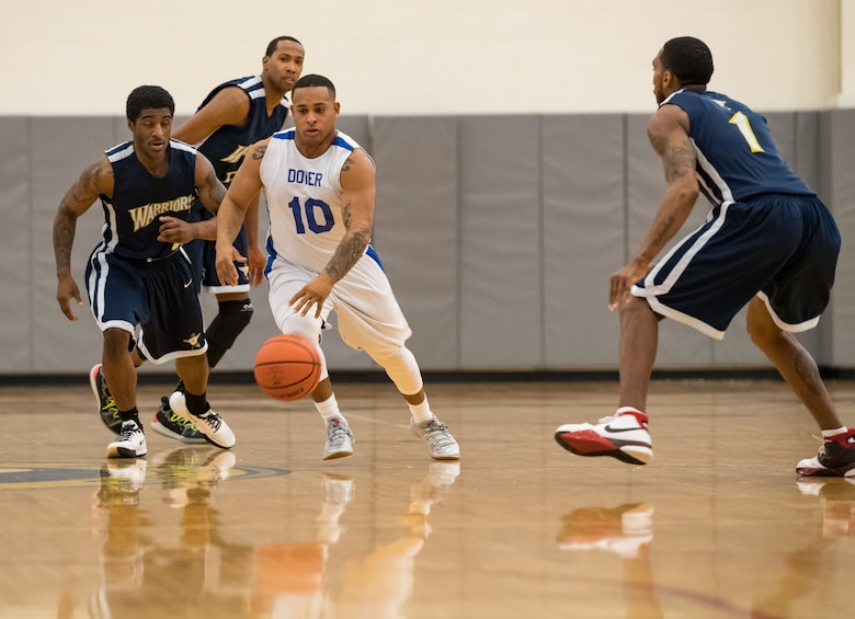 Dover Air Force Base Eagles guard Artis Mitchell (10) dribbles between Matthew Evans and Ryan Coleman (1), guards for the Naval Support Activity Bethesda Warriors, during the Washington Area Military Athletic Conference game Jan. 12, 2020, at the Fitness Center on Dover Air Force Base, Del. The Warriors topped the Eagles, 88-70. (U.S. Air Force photo by Roland Balik)