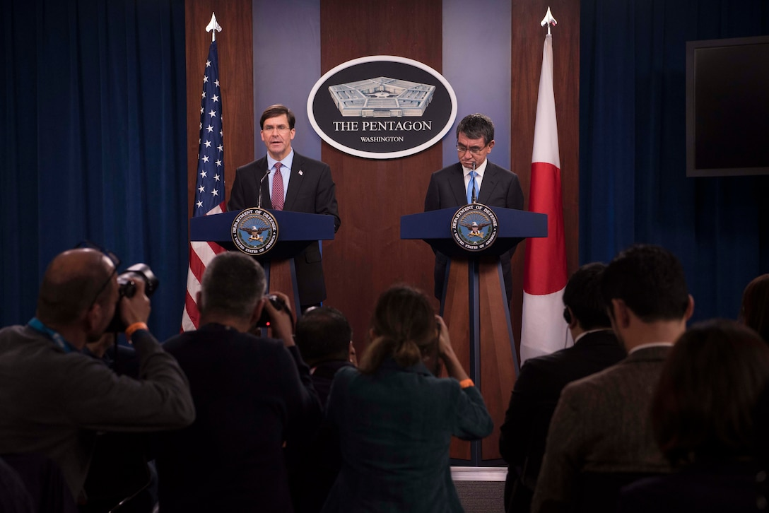 Defense Secretary Dr. Mark T. Esper and another person speak on stage while being photographed.