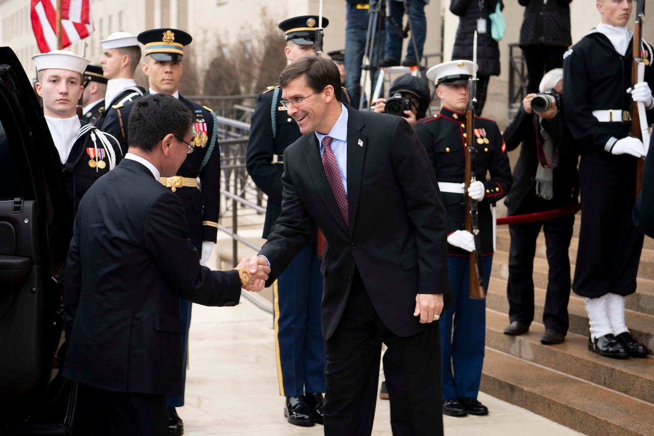 Defense Secretary Dr. Mark T. Esper shakes hands with another civilian outside the Pentagon.