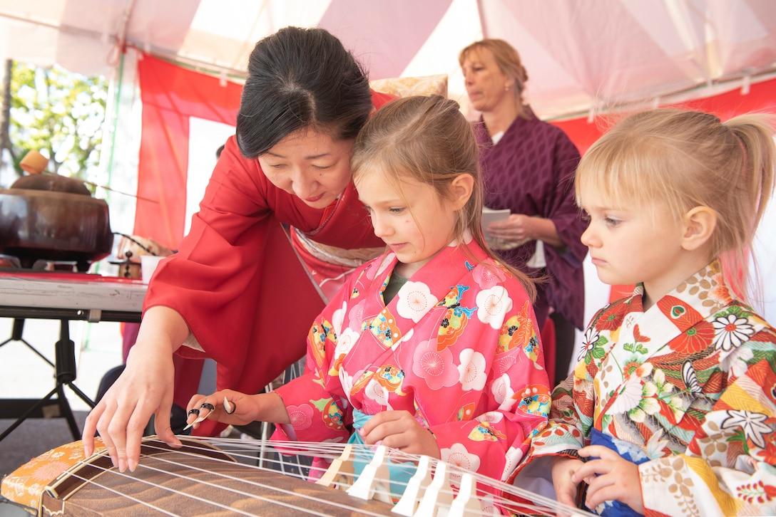 Children learn how to play the Koto, a traditional Japanese harp, from a Japanese employee during the New Year Fest hosted by the Japanese Welfare Association, Jan.10, 2020, at Yokota Air Base, Japan.