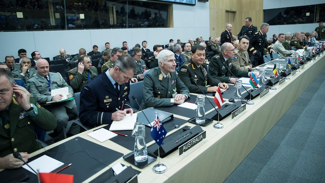 Military officers from various nations sit behind microphones at a round table with lothers seated behind them.