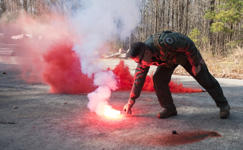 U.S. Air Force Lt. Col. Jonathan Kuntz, 633rd 1st Operations Support Squadron director of operations, places a flare on the ground during a training at Joint Base Langley-Eustis, Virginia, Dec. 12, 2019. The flares are able to be activated in any location in the world during the day or night. (U.S. Air Force photo by Airman 1st Class Sarah Dowe)