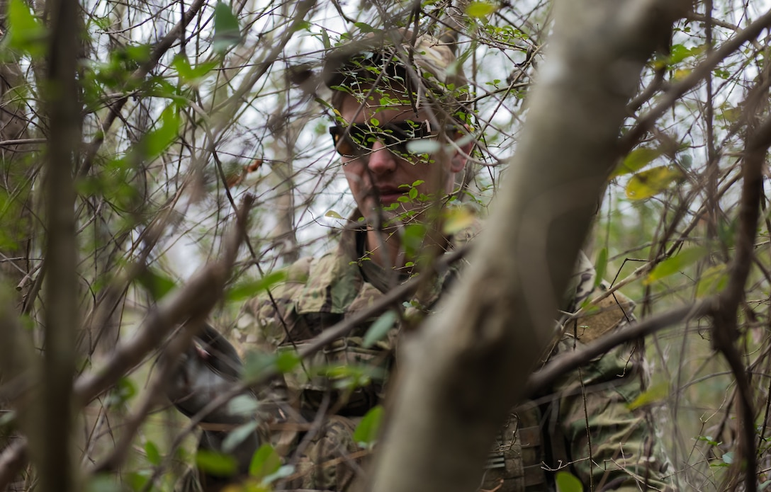U.S. Air Force Tech. Sgt. Stephen Drakes, 192 Operations Support Squadron, Virginia Air National Guard SERE Survival, Evasion, Resistance and Escape non-commissioned officer in charge, demonstrates camouflaging techniques during a training at Joint Base Langley-Eustis, Virginia, Dec. 12, 2019. The training taught skills needed to survive in a rural or urban area. (U.S. Air Force photo by Airman 1st Class Sarah Dowe)
