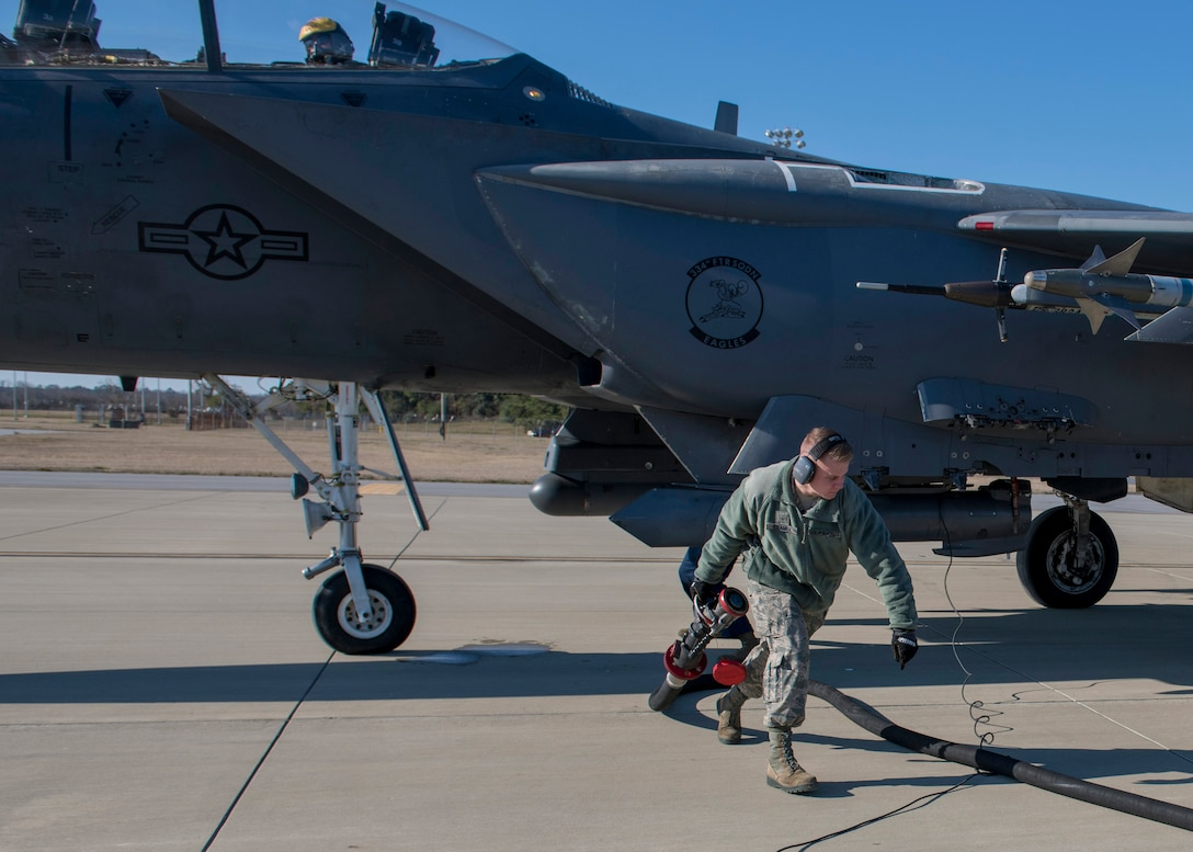 Airman Benjamin Kramer, 4th Logistics Readiness Squadron fuel distribution operator, carries a fuel nozzle after completing a hot-pit refueling of an F-15E Strike Eagle.