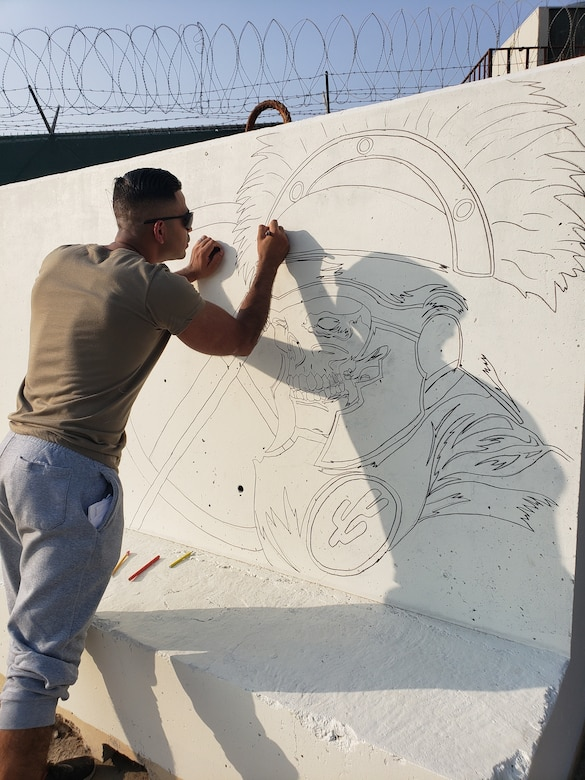 Sgt. Angel Bastidas-Pineda, a transportation land movement non commissioned officer, 103rd Expeditionary Sustainment Command, lays down the first outline of the final t-wall at Camp Arifjan, Nov. 4, 2019. (U.S. Army courtesy photo)