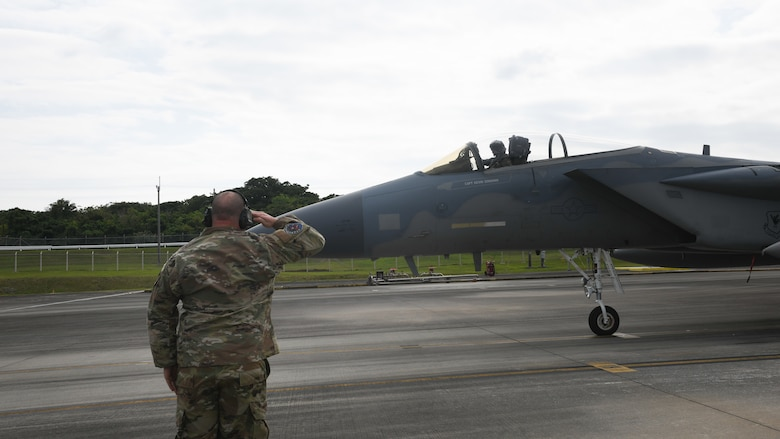 U.S. Air Force Staff. Sgt. Adam Kope, 18th Aircraft Maintenance Squadron, 67th Aircraft Maintenance Unit F-15C Eagle dedicated crew chief, marshals an F-15 Eagle during Exercise Westpac Rumrunner at Marine Corps Air Station Futenma, Jan. 10, 2020. The 18th Wing and its joint partners executed the first WestPac Rumrunner exercise, which focused on defensive counter air capabilities and joint interoperability using agile combat employment concepts. (U.S. Air Force photo by Staff Sgt. Benjamin Raughton)