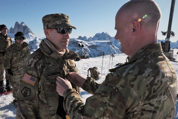 U.S. Army Reserve Lt. Col. Cory D. Poppe, 2500th Digital Liaison Detachment, 7th Mission Support Command, pins rank on Sgt. 1st Class Mark Jacobson, 2500th DLD, 7th MSC, in a mountain-top promotion ceremony after his unit used snowshoes to summit Monte Specie during winter survival training with the Italian Army´s 6th Alpine Regiment during exercise Alpine Rock in Toblach, Italy, January 11, 2020. Fifteen Soldiers from the 2500th participated in the winter survival training that emphasized small-unit tactical interoperability.