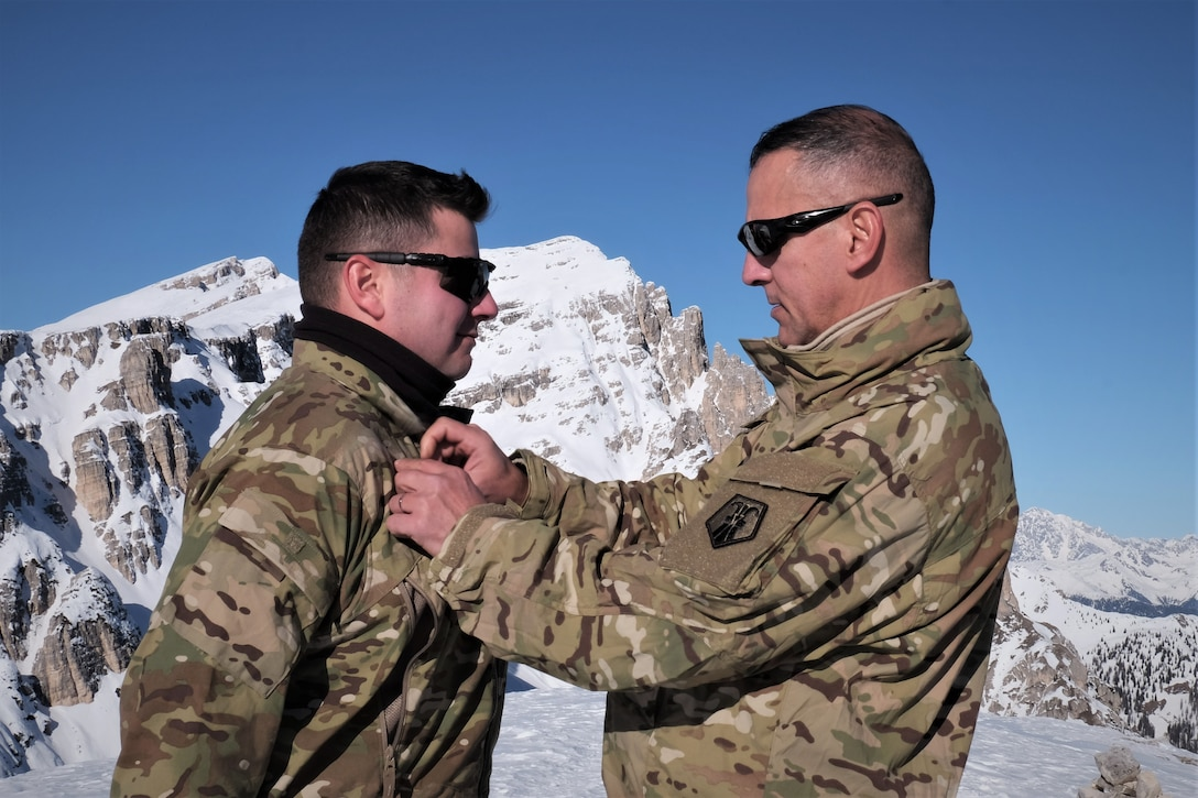 U.S. Army Reserve Master Sgt. Carlos Garcia, 2500th Digital Liaison Detachment, 7th Mission Support Command, pins rank on Staff Sgt. Wesley Cyrus, 2500th DLD, 7th MSC, in a mountain-top promotion ceremony after his unit used snowshoes to summit Monte Specie during winter survival training with the Italian Army´s 6th Alpine Regiment during exercise Alpine Rock in Toblach, Italy, January 11, 2020. Fifteen Soldiers from the 2500th participated in the winter survival training that emphasized small-unit tactical interoperability.