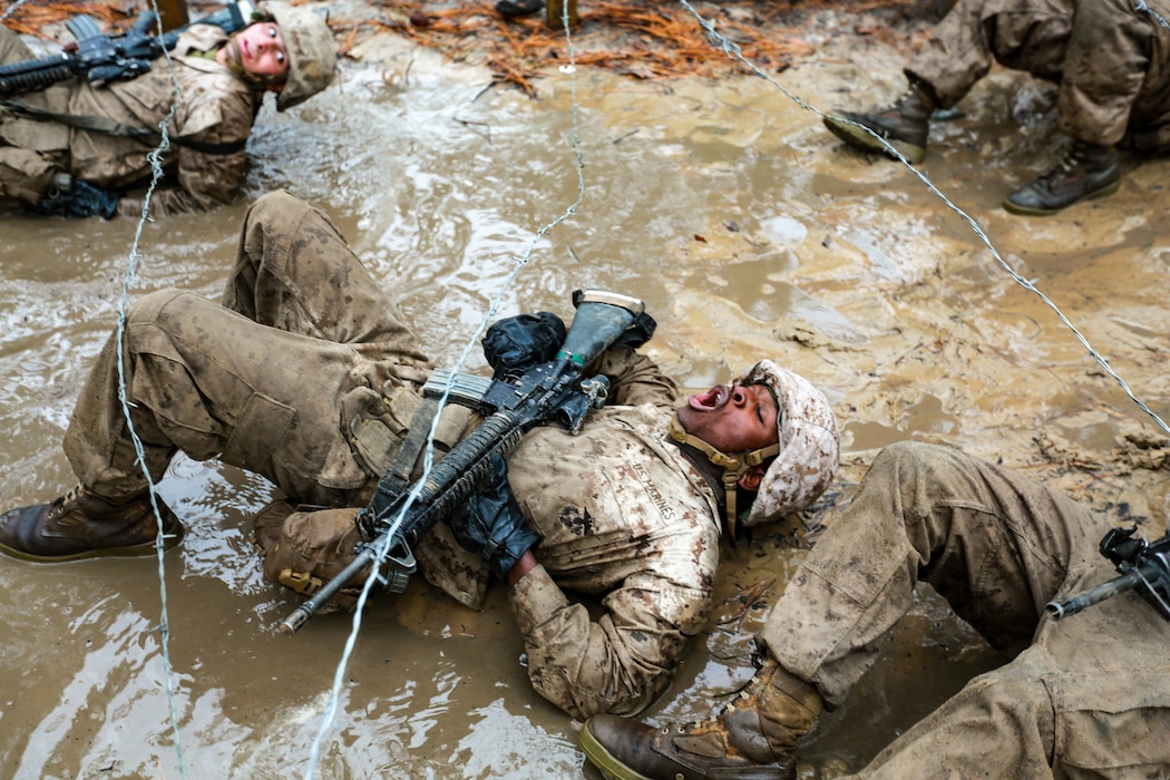 Recruits with Delta Company, 1st Recruit Training Battalion maneuver through mud and barbed wire during the Combat Endurance Course Dec. 21, 2019 at Marine Corps Recruit Depot Parris Island, S.C.