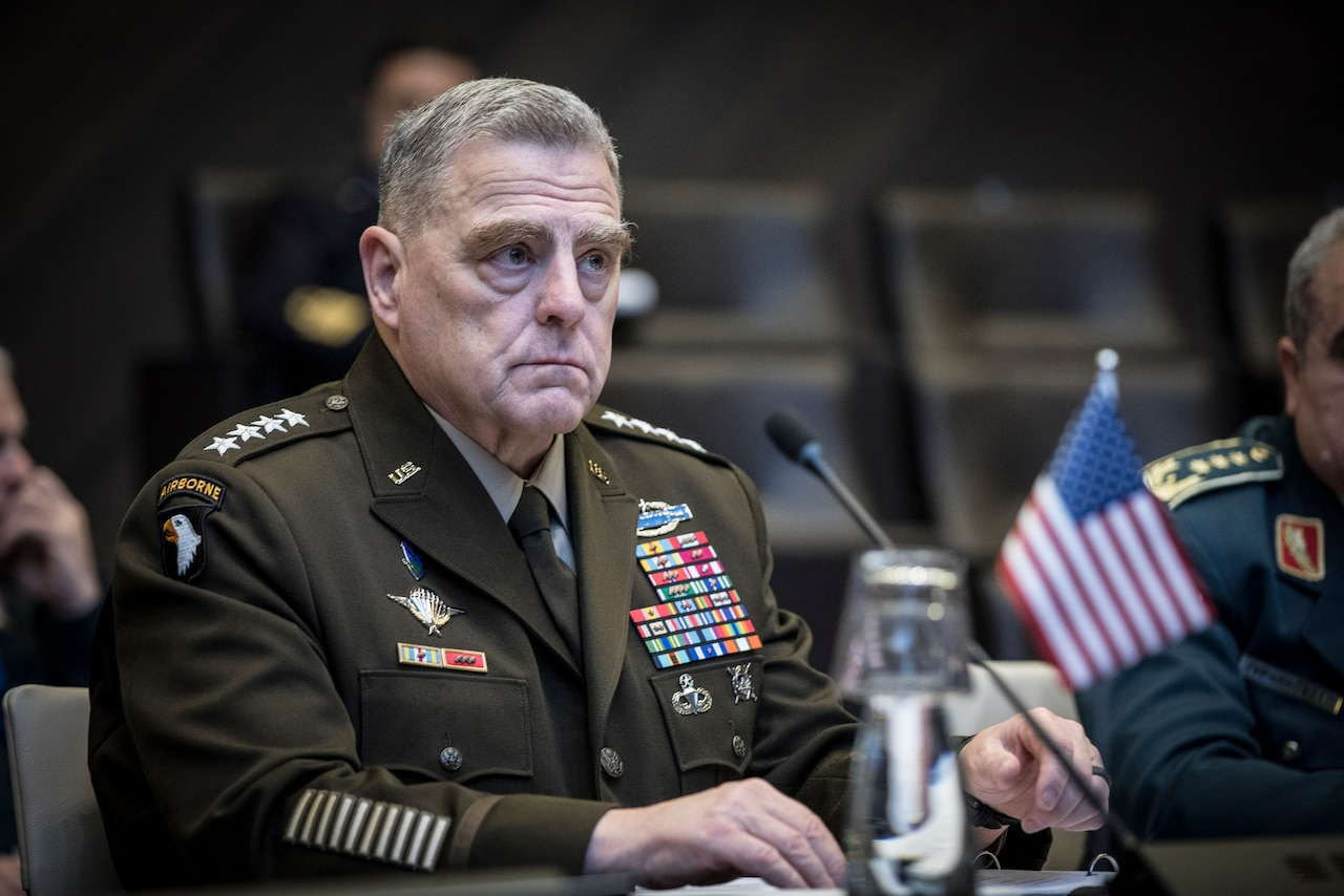 A military officer sits at a table.