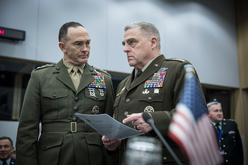 Two military officers speak to each other.