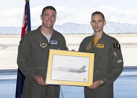 Col. Matthew Renbarger, 56th Operations Group commander (left), presents Lt. Col. Jordon Sander, 61st Fighter Squadron Australian Senior National Representative and new commander of Royal Australian Air Force No. 2 Operational Conversion Unit (No. 2 OCU), an F-35A lithograph during the RAAF Mateship ceremony Nov. 22, 2019, at Luke Air Force Base, Ariz