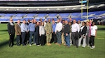 About two dozen people pose as a group standing on a football field.