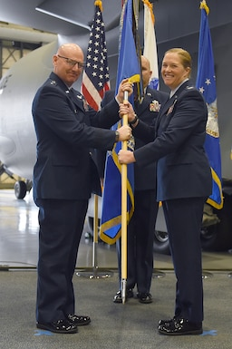 Maj. Gen. Sam Barrett, 18th Air Force commander, hands off the guidon to Col. Erin Staine-Pyne, 62nd Airlift Wing commander, on Joint Base Lewis-McChord, Wash., Jan 10, 2020.