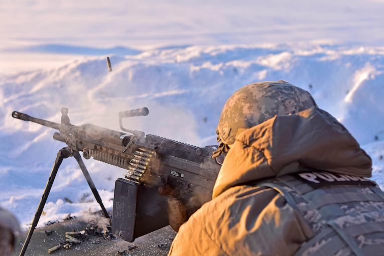 An airman fires a machine gun in a snowy mountainous area.