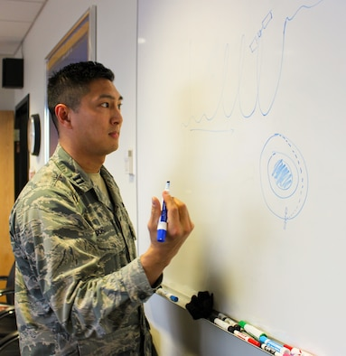Capt. Chris Dong, 1st Space Operations Squadron campaign planner, draws an illustration of the flight path for orbital engagement Jan. 9, 2020. The pattern resembles that of his integrated space common operation picture submitted and selected at Spark Tank. (U.S. Air Force photo by Marcus Hill)