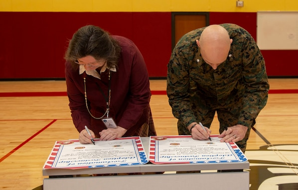 Dana Sutherland, Lejeune High School principal, and Lt. Col. Robert P. Gerbracht, commanding officer, 8th ESB, 2nd MLG, sign a certificate during an Adopt-a-School partnership renewal ceremony, Jan. 7, 2020.