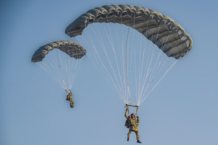 Two airmen descend with parachutes in blue sky.