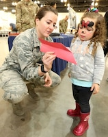 Airman showing young girl a paper airplane.
