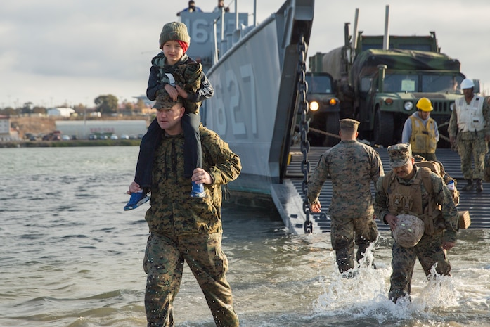 U.S. Marines with the Combat Logistics Battalion 11 (CLB-11), 11th Marine Expeditionary Unit, disembark onto the beach during their homecoming at Camp Pendleton, California, Nov. 26, 2019.
