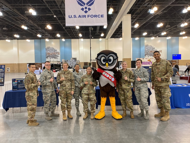 Airmen posing with mascot for group photo.
